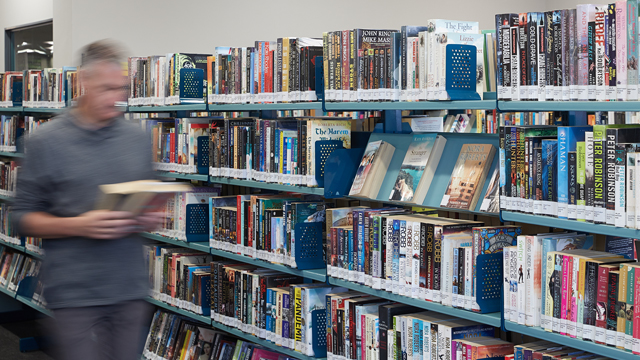 Book shelves with man walking past