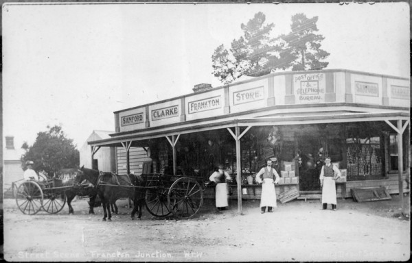 Image of old wooden store. Men in long aprons standing out front, alongside two horse and carts.